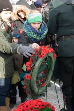 Young girls pin their poppies to the wreaths laid at the Rifles Memorial after the service.