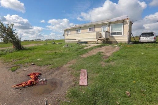A placcard bearing a family name lies in the mud amongst other household items outside of a Waywayseecappo First Nation home with a damaged roof on Tuesday morning. The home is one of seven on the reserve damaged when a tornado touched down on Monday night. (Eva Wasney/The Brandon Sun)