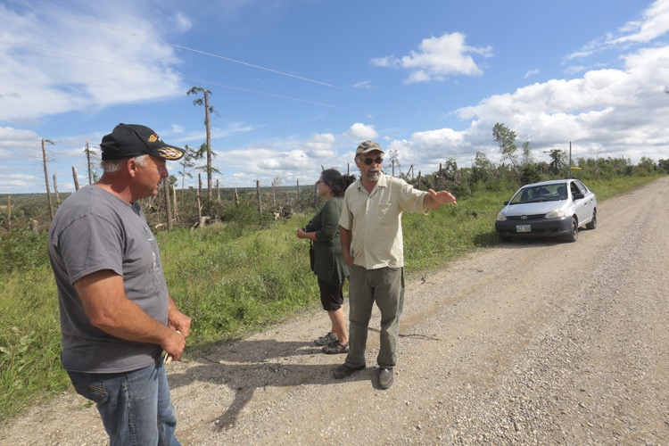 Dennis Tiller, left, listens to neighbour Rick Proven share his experiences during Monday nights tornado east of Erickson while Amy Proven looks at the roughly 1/2 kilometre wide swath of trees toppled during the storm. (Eva Wasney/The Brandon Sun)